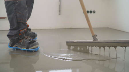 Interior of apartment under construction. Mirror smooth surface of the floor. Floor covering with self leveling cement mortar. Roller application Banque d'images