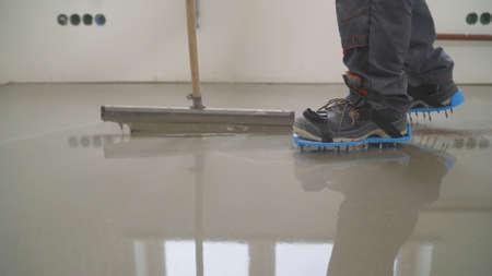 Interior of apartment under construction. Mirror smooth surface of the floor. Floor covering with self leveling cement mortar. Roller application