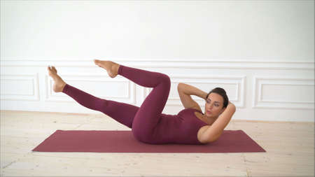 slim mid woman do her fitness exercises. pretty girl working out on floor and holding hands behind. Woman and Pilates.