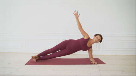 Young woman shows pilates exercises. Young attractive woman practicing yoga at home in studio. Girl shows different poses for yoga. Healthy lifestyle, yoga in my heart, sports every day