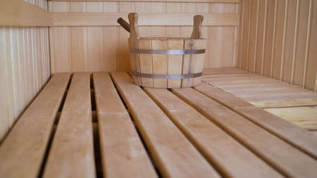 Vennik and wooden bucket in the sauna. Wooden bucket in the interiors of the bath. Sauna room with traditional sauna accessories for healthy.