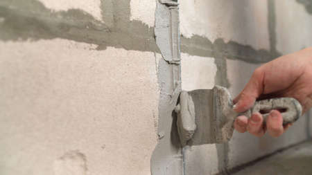 A builder applies plaster with a trowel to a concrete wall to anchor the metal building beacon. The builder applies the plaster with a trowel. Standard-Bild