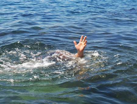 Hand drowning man sticking out of the water