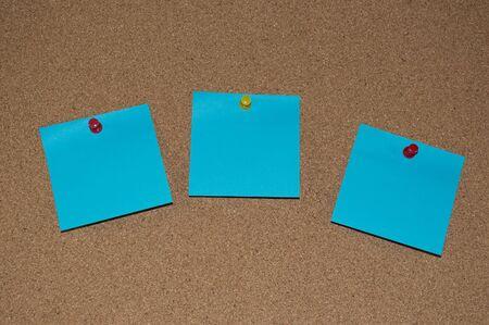 cork board: Blue Post it Notes on a Cork Board