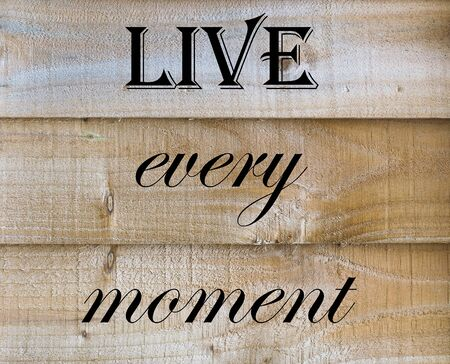 Live Every Moment quote on a wooden background