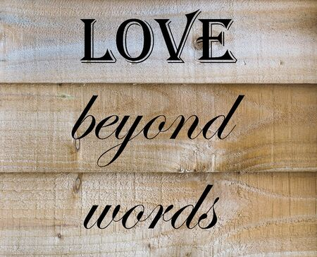 Love Beyond Words quote on Wooden Background