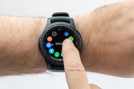 samsung: CHESTER, UK - January 28, 2017: Samsung Gear S3 smartwatch shown on a male wrist and operating the touch screen.