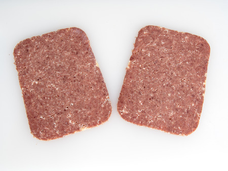 Two slices of Corned Beef on a white background