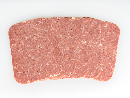 Five slices of Corned Beef on a white background