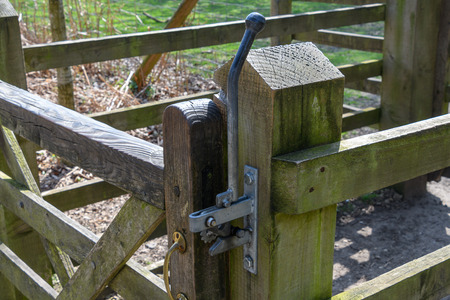 Metal gate post on a wooden forest gate.