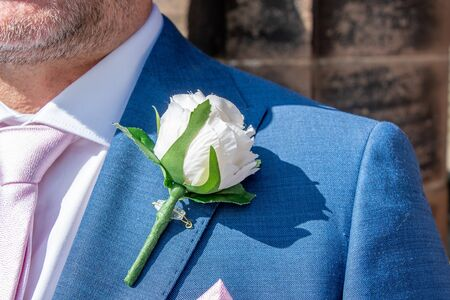 Close view of a groom wearing an artificial rose buttonhole Фото со стока
