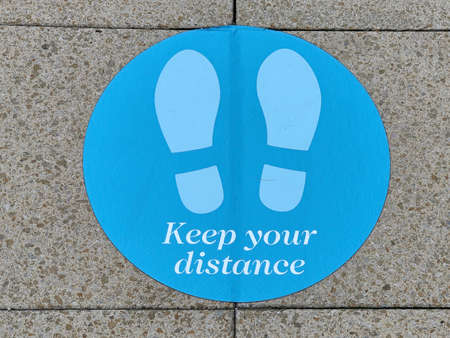Keep your distance stand here sign on a pavement Standard-Bild