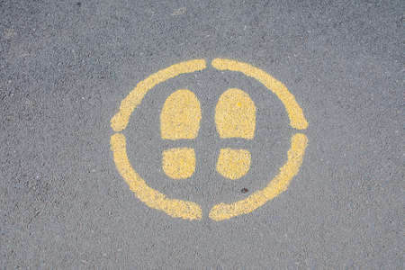 Sign painted on a pavement indicating where to stand