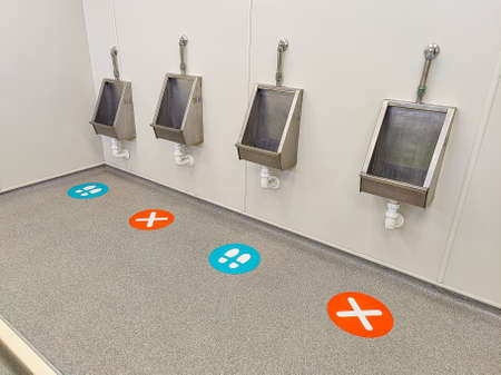 Signs on a floor indicating socal distancing in a mens toilet Standard-Bild