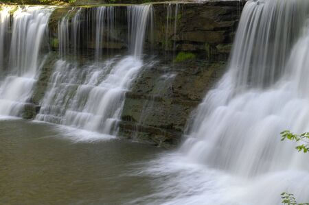 tributary: Water cascades over a rock wall into a lagoon below. Horizontal shot.