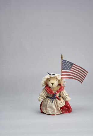 public spirit: Bear doll dressed in red,white and blue holding American flag