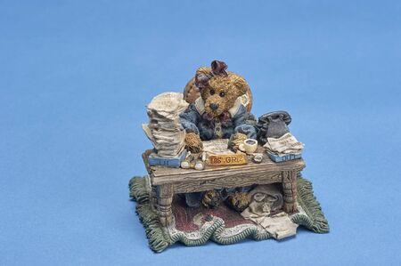 ceramic ornamental figurine depicting bear working hard at cluttered desk
