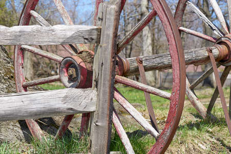 barnyard: conestoga wagon wheel resting against split-rail fence in barnyard