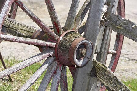 barnyard: conestoga wagon wheel resting against split-rail fence in barnyard