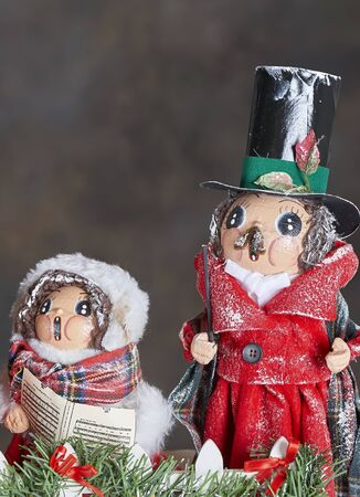 hymn: Christmas Holiday ornaments depicting 19th. century carol singers in the snow Stock Photo