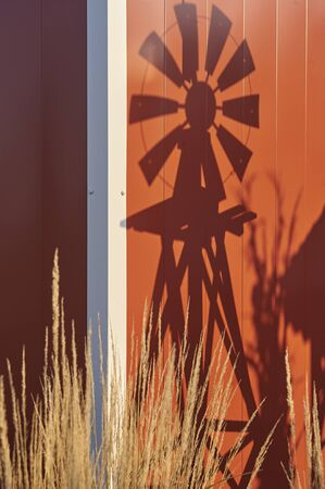 shadow of windmill on side of red barn