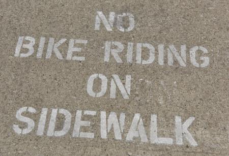 sidewalk warning of no bike riding