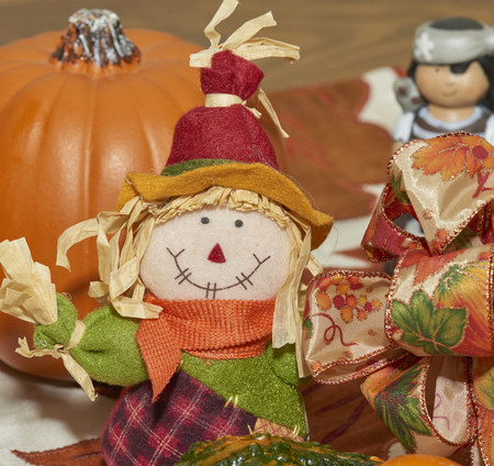 Halloween display with gourds, scarecrow, pumpkin, ribbons and gourd wicker basket