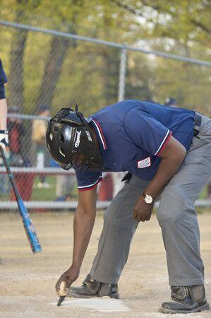 Gesu School vs. SS. Robert & William Catholic Baseball League. Umpire sweeping off home plate
