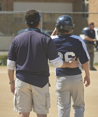 Catholic Middle School Baseball Game. Coach caring for player Stockfoto