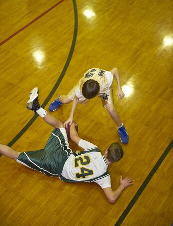 Opponents scrambling for lose ball during youth basketball game