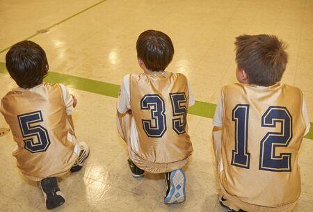 Gesu Catholic School basketball game - team member intently watch basketball game while kneeling on floor