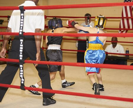 youth boxers sparing in ring with referee.