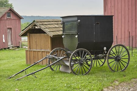 amish buggy parked next to barn