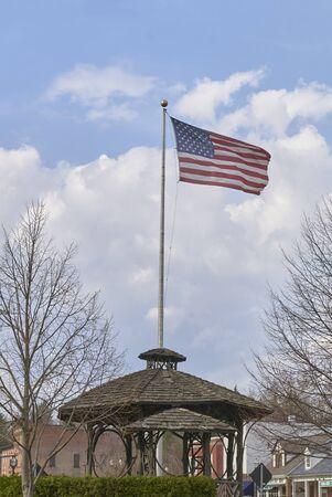 American flag, the stars and stripes, flying over gazebo in rural community center