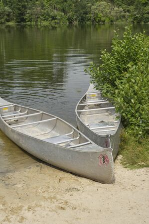 two aluminum canoes on beach of small pond