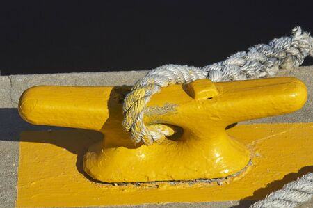 yellow rope cleat on concrete dock