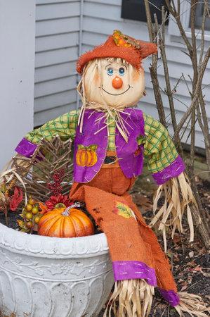 scarecrow doll sitting on planter