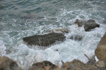 breaking: Waves crashing on the rocks in the blue ocean Stock Photo