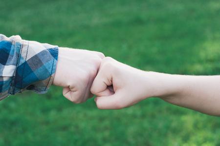 Adolescents donnant un coup de poing lors d'une réunion Banque d'images