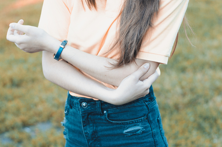 Woman touching elbow. Arm ache outdoors, injured arm Stock Photo