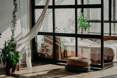 Bedroom loft interior. Bed, pillows, green plant and wall with bricks Фото со стока