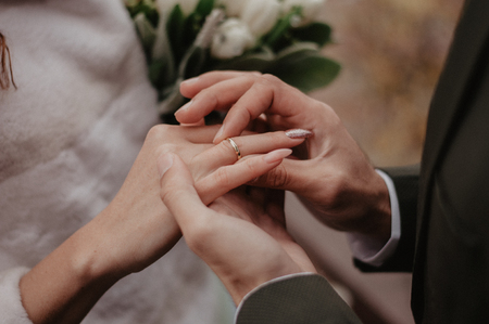 Groom wears golden wedding ring on the bride finger. Wedding ceremony