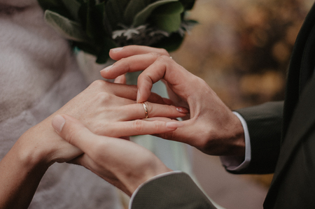 Man holding bride's hand with gold wedding ring. Engagement closeup Фото со стока