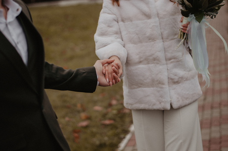 Bride and groom holding hands after wedding ceremony. Woman with wedding bouquet