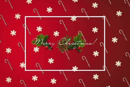 Merry Christmas greeting card with white border. Holiday card with canes and snowflakes pattern, pine branches and balls. Фото со стока