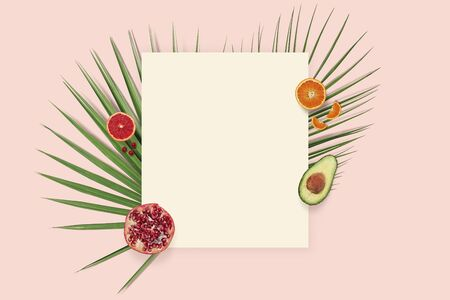Summer holiday card copyspace. Fruit flatlay top view with paper on the pink background. Pomegranate, orange, avocado