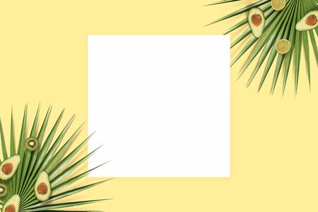 Summer holiday card copyspace. Fruit flatlay top view with paper on the yellow background. Kiwi, avocado and palm leaves Фото со стока