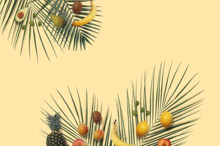 Summer fruits flat lay with copy space on the yellow minimal background. Banana, lemon, peach, pineapple, kiwi, grape, avocado on the green palm leaves Фото со стока