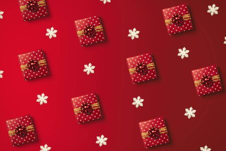 Christmas pattern with red wrapped gift and white snowflakes on the red background