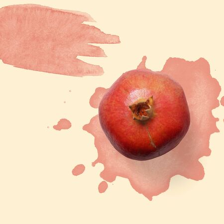 Red pomegranate on the pastel background with red watercolor splash